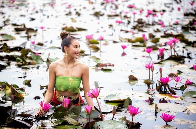 Mujer que sostiene la flor rosada en el lago