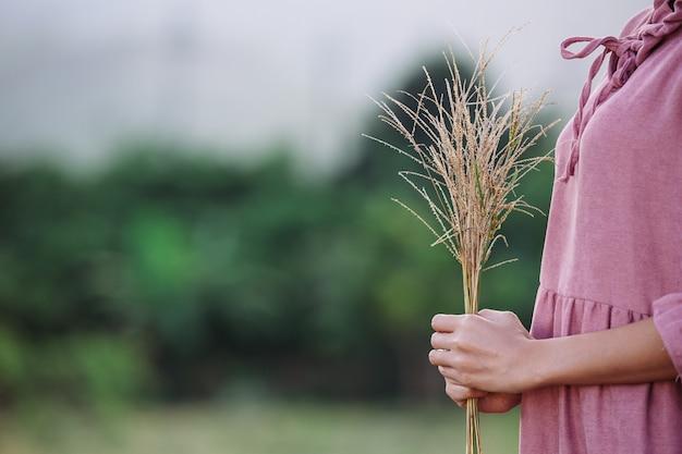 Mujer que sostiene las flores en el prado.