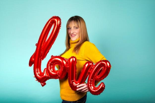 Mujer que sostiene el globo con la palabra amor