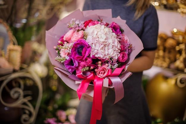 Mujer que sostiene un hermoso ramo de flores rosadas