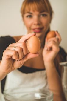 Mujer que sostiene el huevo marrón