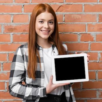 Mujer que sostiene el ipad en blanco