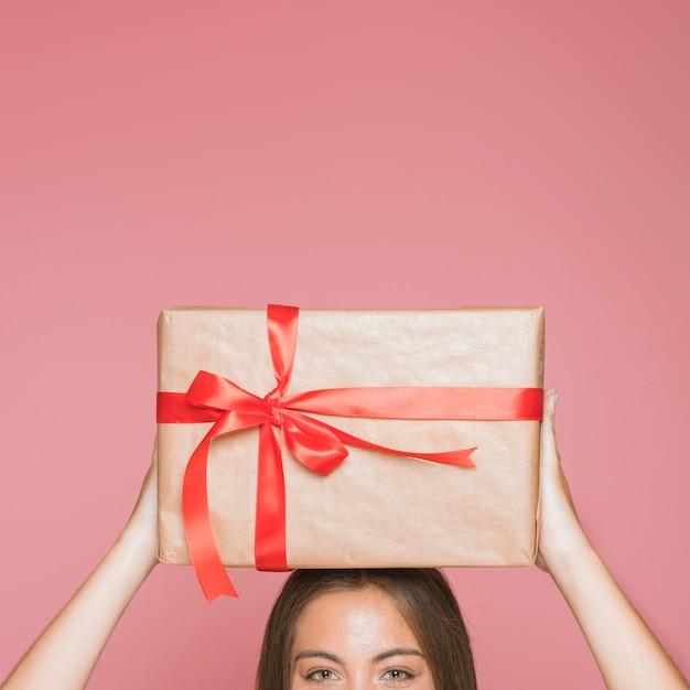 Mujer que sostiene la caja de regalo envuelta sobre su cabeza contra fondo rosado