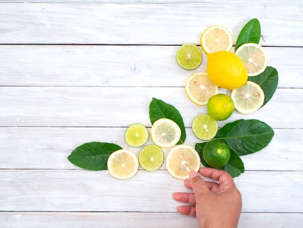 Mujer que sostiene el limón fresco en la tabla blanca