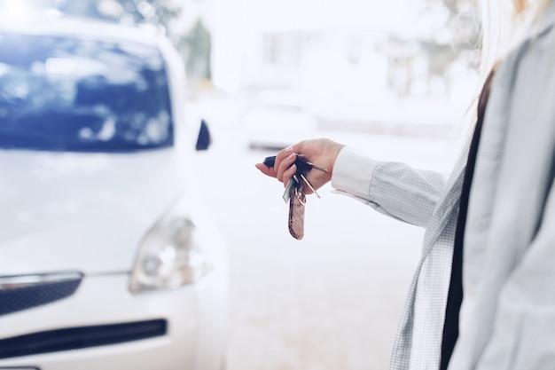 Mujer que sostiene la llave del coche para abrir la puerta del coche.