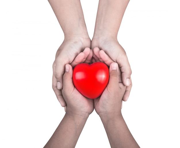 Mujer que sostiene las manos de los niños pequeños y apoya la forma del corazón rojo