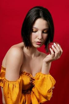 Mujer que sostiene la manzana en la mano