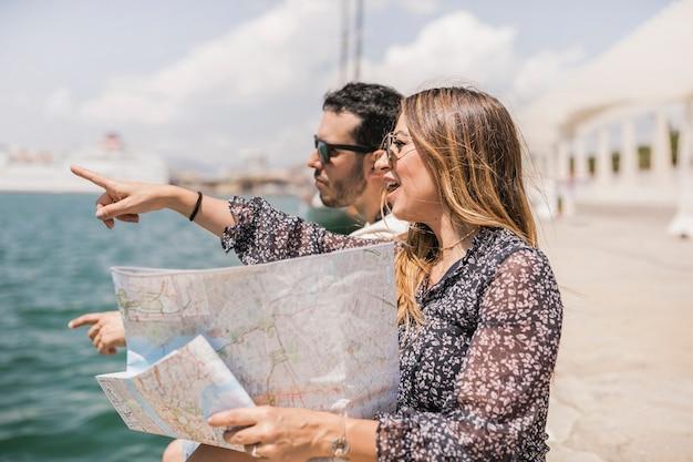 Mujer que sostiene el mapa que señala el dedo en algo que se sienta con su novio en el embarcadero