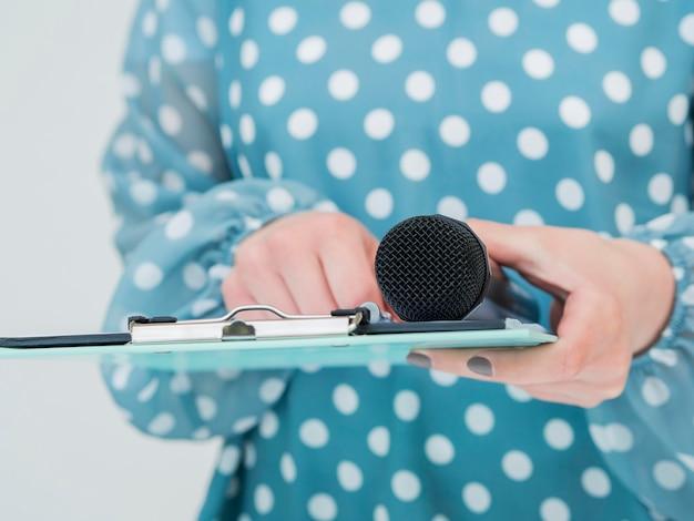 Mujer que sostiene el micrófono y el portapapeles