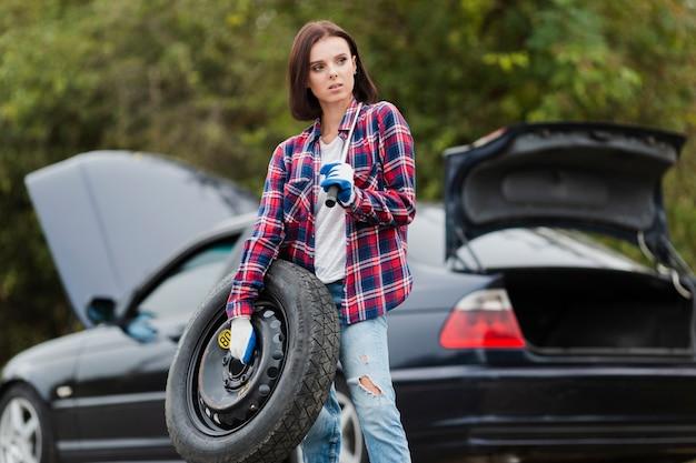 Mujer que sostiene el neumático de repuesto y la llave