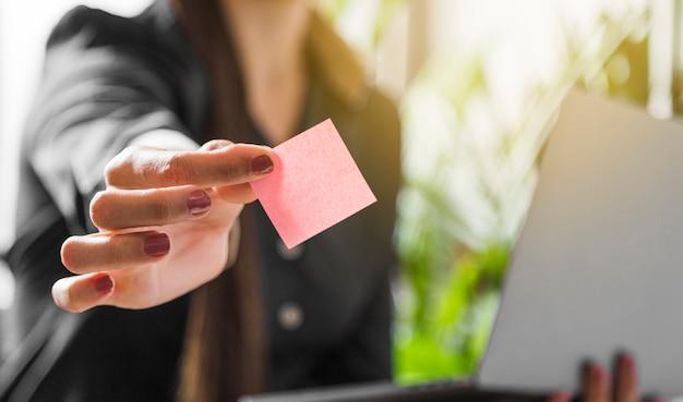 Mujer que sostiene una nota adhesiva con fondo borroso