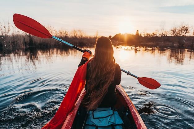 Mujer que sostiene la paleta en un kayak en el río