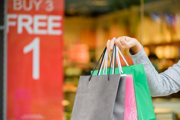 Mujer que sostiene los panieres en la alameda de compras, concepto de la venta de black friday.