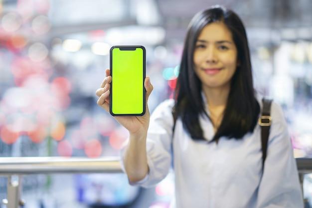 Mujer que sostiene la pantalla verde en blanco del teléfono inteligente en el móvil
