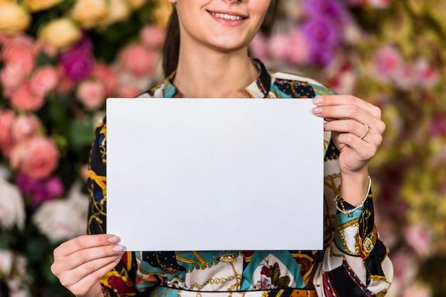 Mujer que sostiene el papel en blanco en casa verde