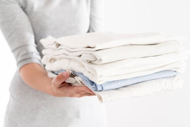 Mujer que sostiene la pila limpia de ropa