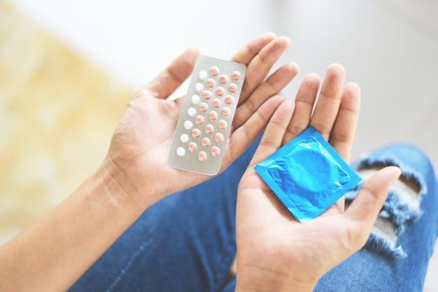 Mujer que sostiene píldoras anticonceptivas y condón