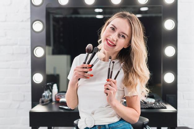 Mujer que sostiene pinceles de maquillaje en estudio