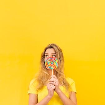 Mujer que sostiene la piruleta colorida