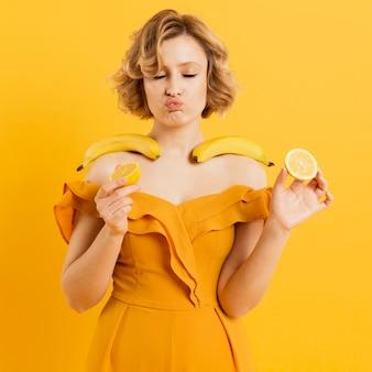 Mujer que sostiene plátanos y limón