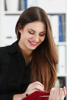 Mujer que sostiene la pluma de plata lista para hacer nota en hoja abierta del cuaderno. la empresaria en traje en el espacio de trabajo hace registros de pensamientos en el organizador personal, conferencia de cuello blanco, concepto de firma