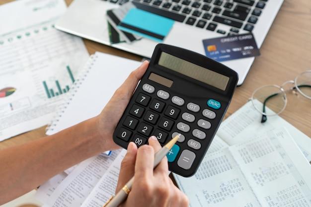 Mujer que sostiene y que usa la calculadora, la cuenta y el concepto de ahorro.