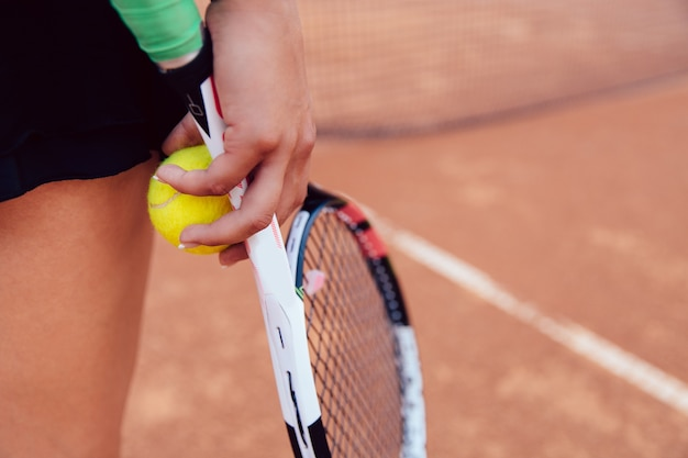 Mujer que sostiene la raqueta y la bola de tenis en la corte de arcilla.