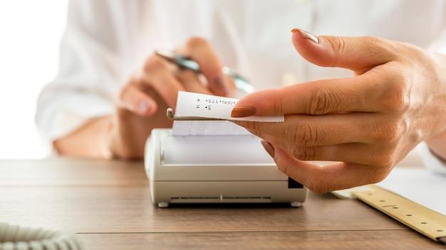 Mujer que sostiene un recibo impreso cuando sale de la máquina sumadora