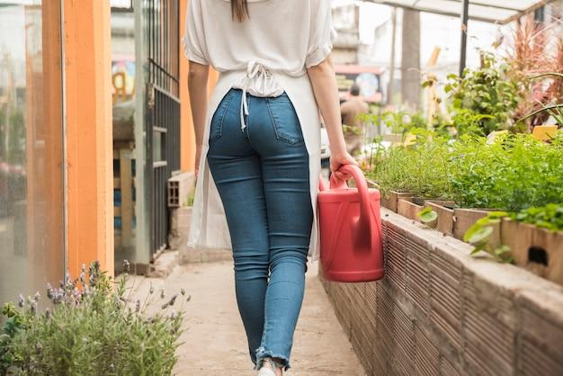 Mujer que sostiene la regadera roja en invernadero