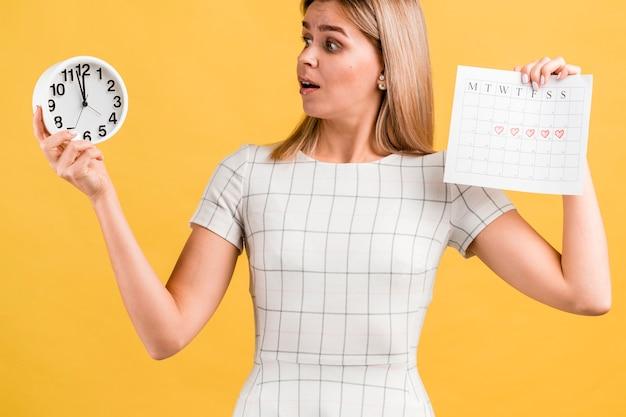 Mujer que sostiene un reloj y su calendario de época