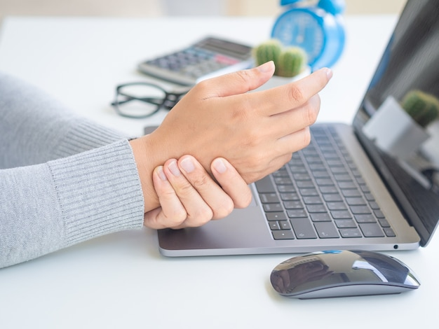 Mujer que sostiene su dolor de muñeca de usar la computadora por mucho tiempo.