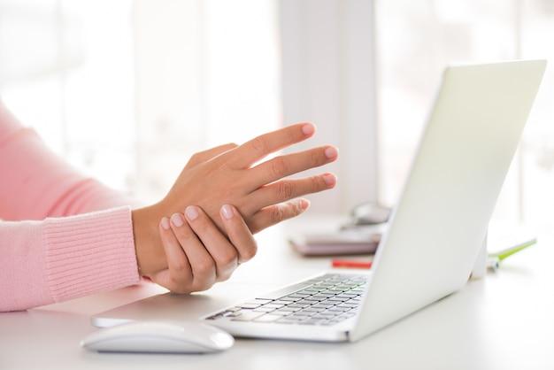 Mujer que sostiene su dolor de muñeca de usar la computadora. síndrome de la oficina.