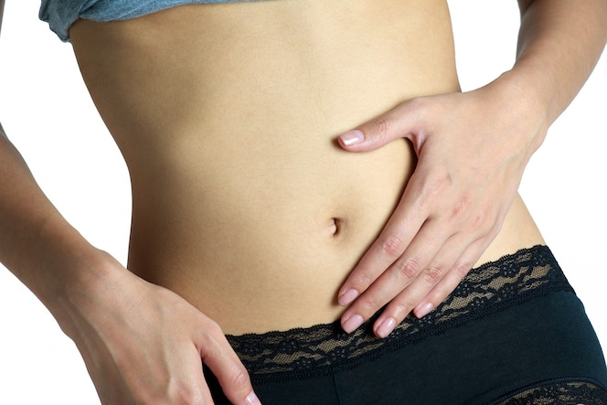 Mujer que sostiene su vientre en el área del dolor aislada en el fondo blanco.