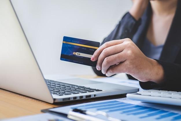 La mujer que sostiene la tarjeta de crédito y escribe en la computadora portátil para compras en línea y el pago realiza una compra