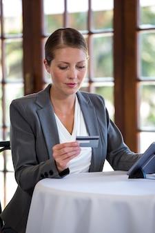 Mujer que sostiene la tarjeta de crédito y la tableta