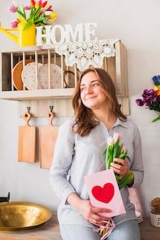 Mujer que sostiene la tarjeta de felicitación y flores