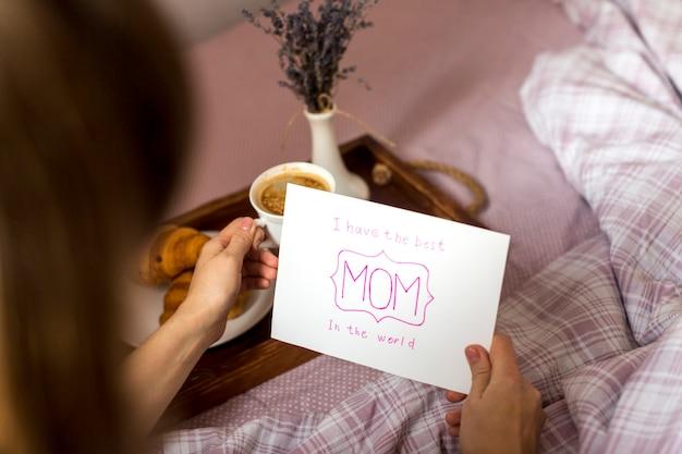 Mujer que sostiene la tarjeta de felicitación y la taza de café en la bandeja