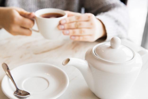 Mujer que sostiene la taza blanca de té en manos. desayuno en mesa blanca en la cafetería.