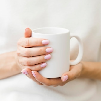 Mujer que sostiene la taza blanca