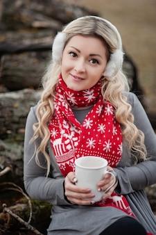 Mujer que sostiene la taza grande con chocolate caliente y bebida de chocolate y malvaviscos.