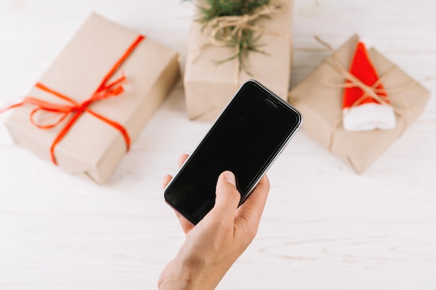 Mujer que sostiene teléfono inteligente por encima de las cajas de regalo