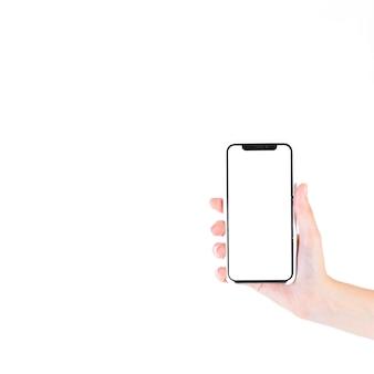 Mujer que sostiene el teléfono inteligente con pantalla blanca en blanco