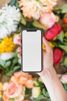Mujer que sostiene teléfono inteligente con pantalla en blanco por encima de las flores