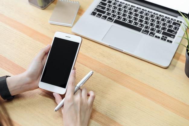 La mujer que sostiene un teléfono de pantalla en blanco y una computadora portátil y pone un reloj inteligente, efecto película.