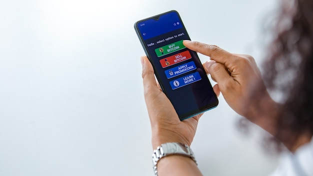 Mujer que sostiene los teléfonos inteligentes y usa el toque del dedo en la pantalla y selecciona los botones de la aplicación de compra y venta para el comercio de dinero digital de bitcoin o criptomoneda con espacio de copia
