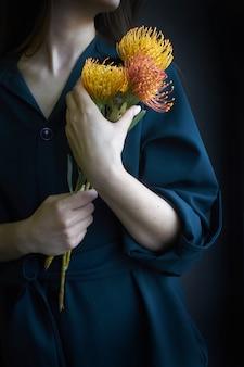 Mujer que sostiene tres proteas amarillas y anaranjadas