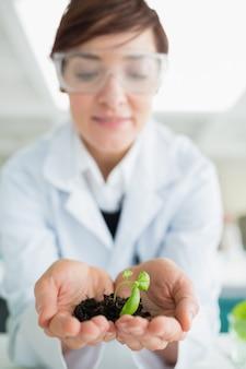 Mujer que sostiene una pequeña planta con suelo