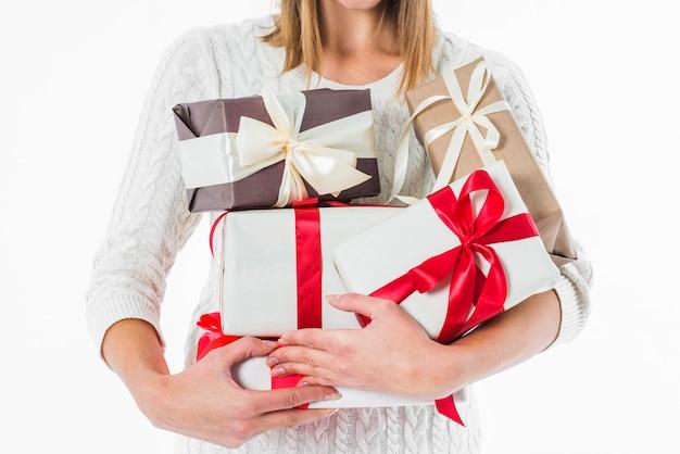 Mujer que sostiene varias cajas de regalo en las manos