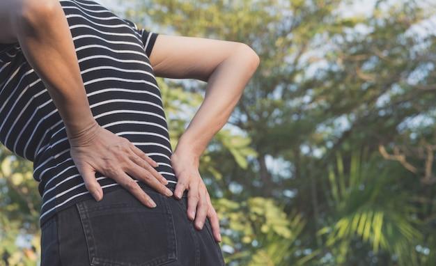 Una mujer que sufre de dolor de espalda, lesión en la columna vertebral y problemas musculares al aire libre.