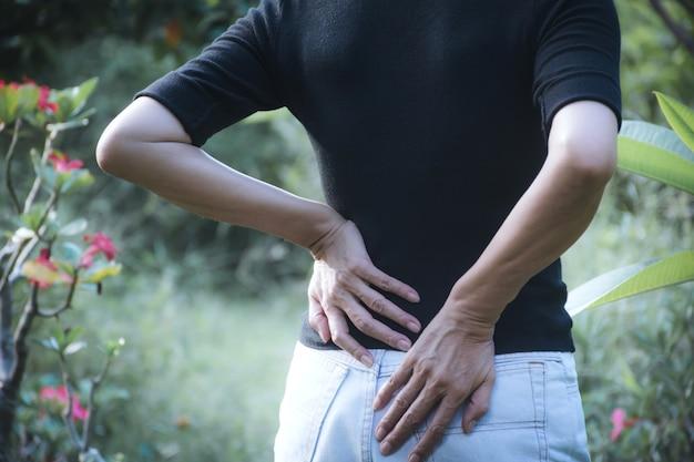 Una mujer que sufre de dolor de espalda, lesión en la columna vertebral y problemas de problemas musculares